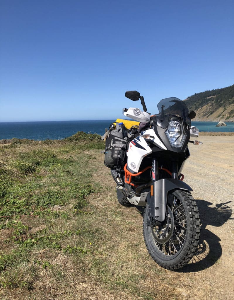 KTM 1090 adventuree R on the dusty highway with the blue pacific ocean behind