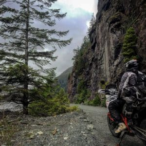 Adventure motorcycle tour on northern vancouver island, a rider passes a cliff face and a remote lake.